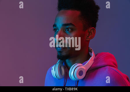Portrait of casual african american man in colorful hoodie posing with headphones isolated over violet background - Stock Photo