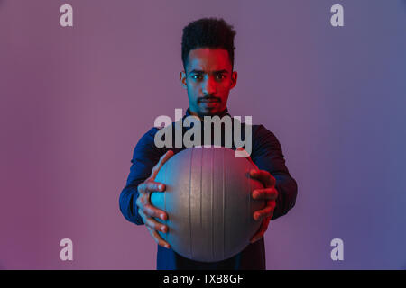 Portrait of serious african american man in sportswear poising at camera with fitball isolated over violet background - Stock Photo