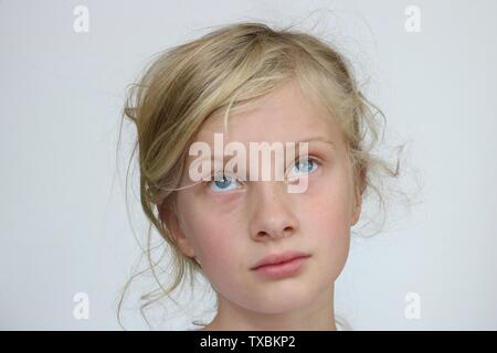 Portrait of a young blond blue eyed girl looking up thinking against a white background - Stock Photo