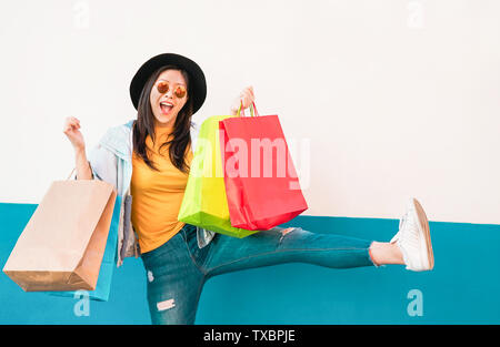Crazy fashion Asian girl doing shopping in mall center - Happy Chinese woman having fun buying new clothes - Stock Photo