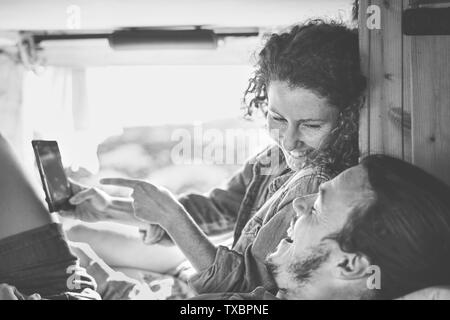 Happy couple watching on their mobile phone in minivan with wood interior - Man and woman using smartphone during their journey - Stock Photo