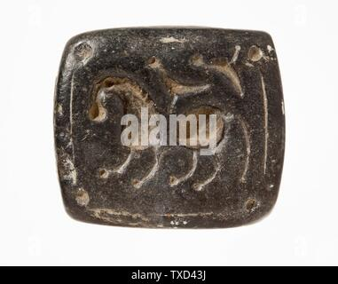 'Stamp Seal, Tabloid (image 1 of 2); Tools and Equipment; seals Black serpentine Height:  7/16 in. (1 cm); Width:  1 5/16 in. (3.3 cm); Length:  1 1/2 in. (3.7 cm) Gift of Nasli M. Heeramaneck (M.76.174.572) Art of the Ancient Near East; circa 2nd millennium B.C.; ' - Stock Photo