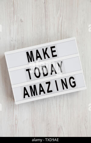 'Make today amazing' words on a modern board on a white wooden surface. From above, overhead, flat lay, top view. Closeup. - Stock Photo