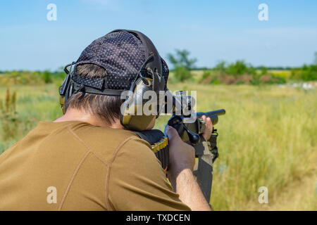 The shooter in a brown T-shirt and a baseball cap aims from a rifle - Stock Photo