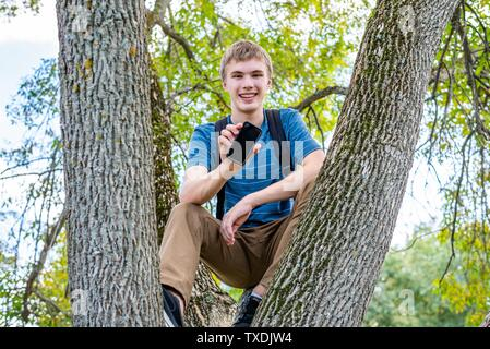 Happy teenager sitting on a tree branch in a park and holding his cell phone. - Stock Photo