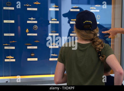 Submarine Force Museum, Groton CT USA, Jun 2019. Grandkids looking at different submarine insignia from other countries with grandfather. - Stock Photo