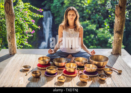 Woman playing on Tibetan singing bowl while sitting on yoga mat against a waterfall. Vintage tonned. Beautiful girl with mala beads meditating - Stock Photo