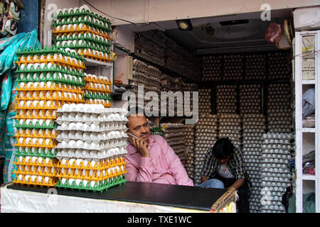 Egg Seller on his Mobile phone inside his Eggs Only Store - Stock Photo