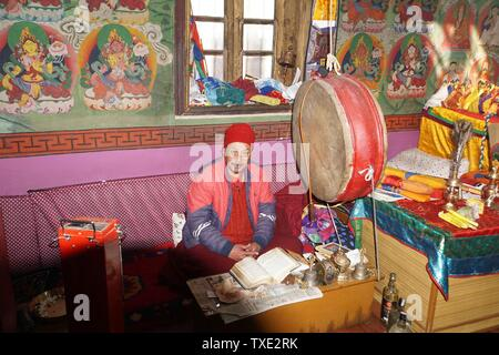 Monk seated next to a Big Drum in the Colourful Interior of Lochawa La-Khang Buddhist Monastery - Stock Photo