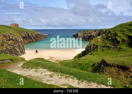 A cyclist enjoys a sunny day on deserted beach in the Outer Hebrides - Stock Photo