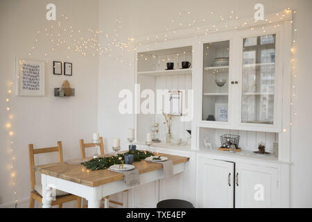 Festively laid white table and chairs in living room - Stock Photo