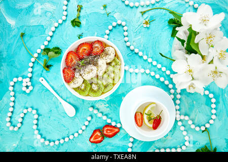 Healthy breakfast bowl smoothie with strawberry, banana, kiwi  and chia seeds on blue background. Healthy vegan food concept. - Stock Photo