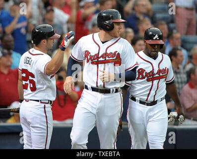 Atlanta Braves' Freddie Freeman (C) and Justin Upton are congratulated at the plate by batter Dan Uggla (26) after scoring against the Colorado Rockies in the third inning at Turner Field in Atlanta, July 29, 2013. UPI/David Tulis - Stock Photo