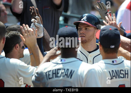 Atlanta Braves' Freddie Freeman is congratulated by teammates in the dugout after he hits a three-run homer against the Miami Marlins in the fifth inning at Turner Field in Atlanta, August 11, 2013. Freeman upped his home run total to 14 on the season.  UPI/David Tulis - Stock Photo