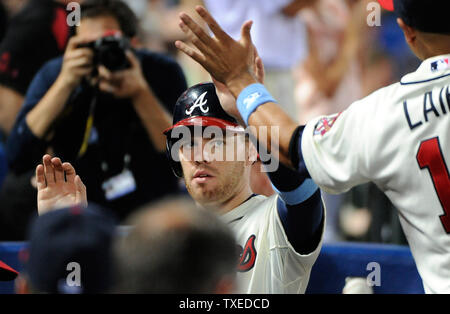 Atlanta Braves' Freddie Freeman (center) is congratulated in the dugout after scoring on teammate Tommy La Stella's two RBI double against the Los Angeles Angels in the sixth inning at Turner Field in Atlanta, June 15, 2014. UPI/David Tulis - Stock Photo