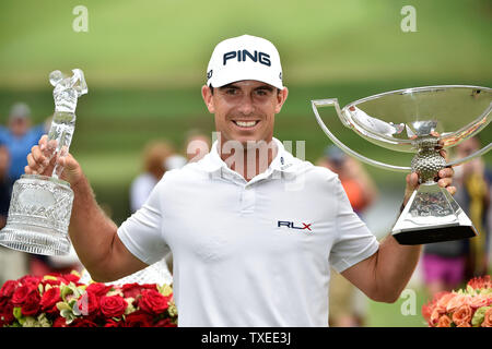 Billy Horschel hoists both the FedEx Cup trophy (R) and the PGA Tour Championship trophy by posting an 11-under-par score, three strokes ahead of Rory McIlroy and Jim Furyk, at East Lake Golf Club on September 14, 2014, in Atlanta. Horschel also brought home a $10 million bonus for his playoff win. UPI/David Tulis - Stock Photo