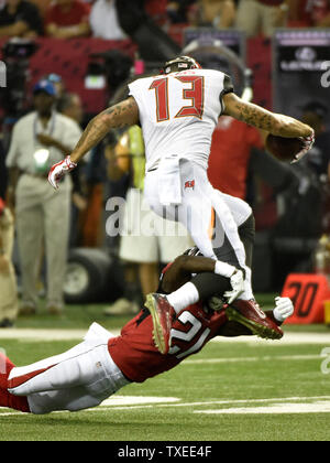Atlanta Falcons' Desmond Trufant (21) grabs Tampa Bay Buccaneers receiver Mike Evans (13) by the legs during the first half of their football game at the Georgia Dome in Atlanta on September 18, 2014. UPI/David Tulis - Stock Photo
