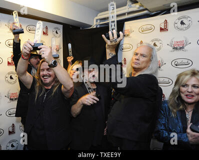 Lynyrd Skynyrd, including Johnny Colt, Johnny Van Zant, Dale Rossington, Gary Rossington, Rickey Medlocke, and Carol Chase (L-R) show off their Fox Theatre awards after arriving for ÒOne More For The Fans! - Celebrating The Songs & Music of Lynyrd Skynyrd,' a special concert featuring once-in-a-lifetime collaborations by friends and admirers paying tribute to Lynyrd SkynyrdÕs four decades of southern-based rock music at the Fox Theatre in Atlanta on November 12, 2014. The band's live album recorded in the theatre 40 years ago helped save the historic structure from destruction. UPI/David Tulis - Stock Photo