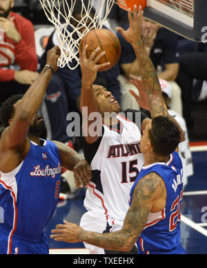 Atlanta Hawks' Al Horford (15) is blocked by Los Angeles Clippers' DeAndre Jordan (6) and Matt Barnes (R) during the first half of their NBA game at Philips Arena in Atlanta, December 23, 2014. UPI/David Tulis - Stock Photo