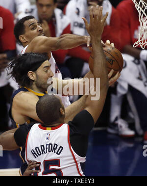 Indiana Pacers' Luis Scola (C) is blocked by Atlanta Hawks' Al Horford (15) and Thabo Sefolosha (L) during the first half of their NBA game at Philips Arena in Atlanta, January 21, 2015. Photo by David Tulis/UPI - Stock Photo