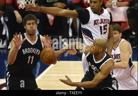 Brooklyn Nets' Jarrett Jack (R) passes around Atlanta Hawks' Al Horford (15) to teammate Brook Lopez (11) during the first half of an NBA game at Philips Arena in Atlanta, January 28, 2015. Photo by David Tulis/UPI - Stock Photo