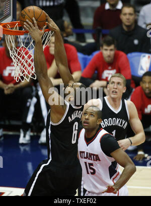 Brooklyn Nets' Alan Anderson (6) dunks over Atlanta Hawks' Al Horford (15) during the first half of an NBA game at Philips Arena in Atlanta, January 28, 2015. Photo by David Tulis/UPI - Stock Photo