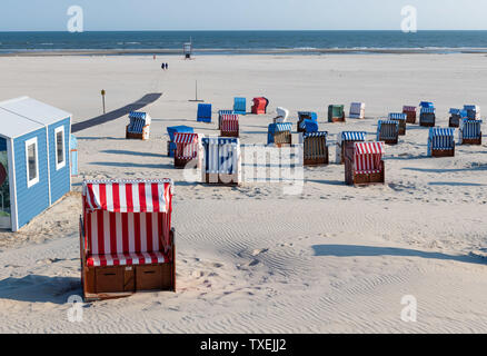 Path to white beach with colorful beach chairs on the Frisian island of Juist. - Stock Photo