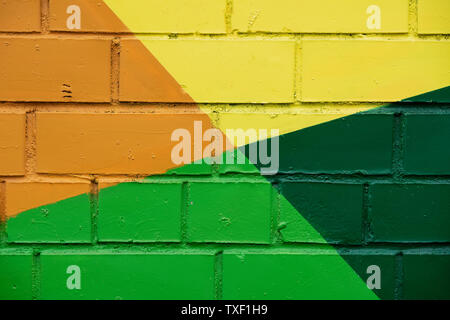 Brick wall is decorated with bright abstract drawings paint closeup. Detail like as graffiti . Fragment for background, stylish picture - Stock Photo