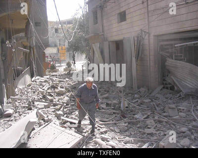 A Lebanese man walks through rubble in the Hezbollah controlled town of Baalbek, in Lebanon's Beqaa Valley hours after a the U.N. brokered cease fire went into effects on August 14, 2006. After the cease-fire went into effect at 08:00 (05:00 GMT) local time tens of thousands of Lebanese refugees packed up their things and headed to their homes in southern Lebanon. (UPI Photo/Hussein Darwish) - Stock Photo