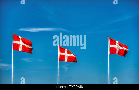 Three Danish flags against a blue sky - Stock Photo