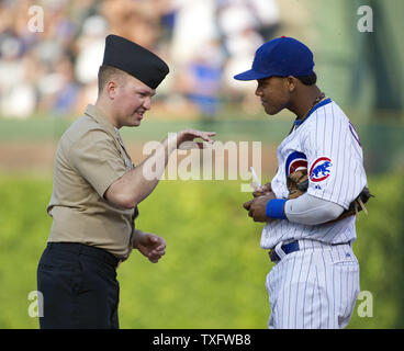 Chicago Cubs shortstop Starlin Castro (R) talks with U.S. Navy Petty Officer 2nd Class William Ellwood before the game against the Chicago White Sox at Wrigley Field on May 19, 2012, in Chicago. Service members took the field right before the game as part of NATO day at Wrigley Field.    UPI/Brian Kersey - Stock Photo