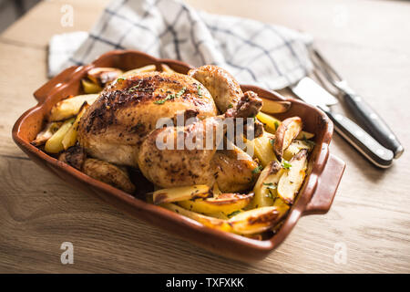 Roasted whole chicken with potatoes in baking dish. Tasty food a - Stock Photo