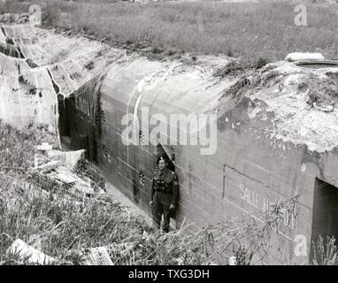 French soldier posing in front of the German bunker in Douvres-la-Délivrande after the defeat of the enemy. June 17, 1944 - Stock Photo