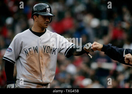 New York Yankees runner Alberton Gonzalez is congratulated by his teammates after scoring in the sixth inning on a wild pitch by Boston Red Sox pitcher Josh Beckett at Fenway Park in Boston, Massachusetts on April 12, 2008.  (UPI Photo/Matthew Healey) - Stock Photo