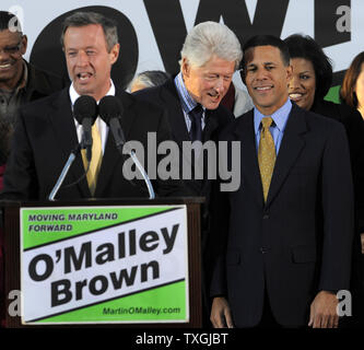 Former U.S. President Bill Clinton (C,background) listens to Maryland's Lt.Gov. Anthony Brown as Maryland Gov. Martin O'Malley makes remarks at the podium, at Federal Hill Park,in Baltimore, Maryland, October 21, 2010.  Clinton has been lending a hand on the campaign trail, as some polls suggest the Democrats may lose majority control of the House in the upcoming midterm elections.        UPI/Mike Theiler - Stock Photo