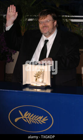 Director Michael Moore acknowledges the cheers of photographers at a photocall after winning the Palme d'Or for his film 'Fahrenheit 911' at the Cannes Film Festival May 22, 2004   in Cannes, France. (UPI Photo/Christine Chew) - Stock Photo