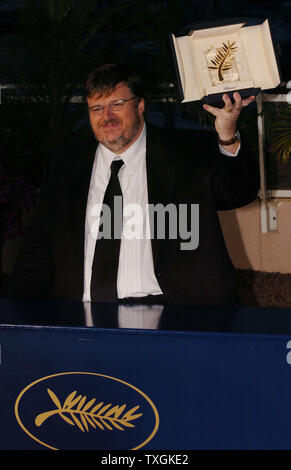 Director Michael Moore holds up his prize for photographers at a photocall after winning the Palme d'Or for his film 'Fahrenheit 911' at the Cannes Film Festival May 22, 2004   in Cannes, France. (UPI Photo/Christine Chew) - Stock Photo