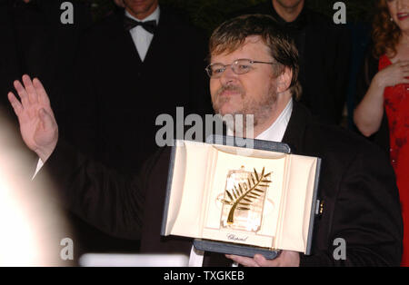 Director Michael Moore acknowledges the cheers of 'Bravo!' from photographers at a photocall after winning the Palme d'Or for his film 'Fahrenheit 911' at the Cannes Film Festival May 22, 2004   in Cannes, France. (UPI Photo/Christine Chew) - Stock Photo