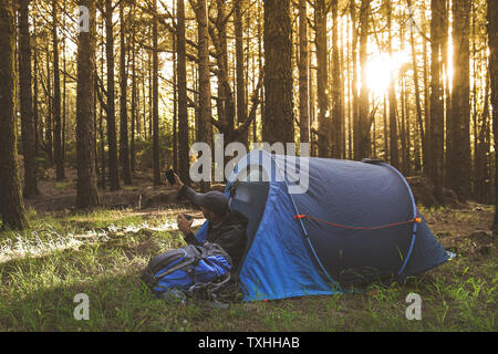 Trendy man making social video story in a camping tent at sunset Tourist boy doing selfie with phone in the forest to share with friend Tourism advent - Stock Photo
