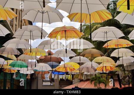 Beautiful set of umbrellas hanging in Caudan Waterfront street, Mauritius. - Stock Photo