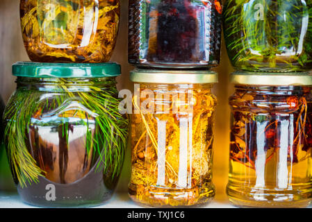 Jars with honey and natural colorful herbs for sale on shelves - Stock Photo