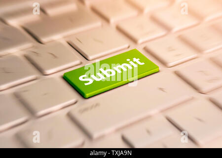 Submit Button. Keyboard Concept. Green Button on grey Computer Keyboard. blurred in motion background. - Stock Photo