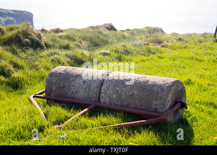 old rustic concrete roller abandoned at a field in ireland - Stock Photo