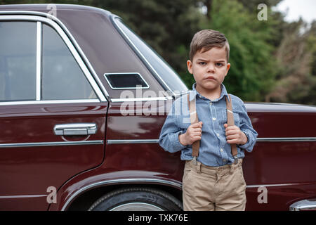Caucasian little boy in vintage clothes standing next to a retro car - Stock Photo