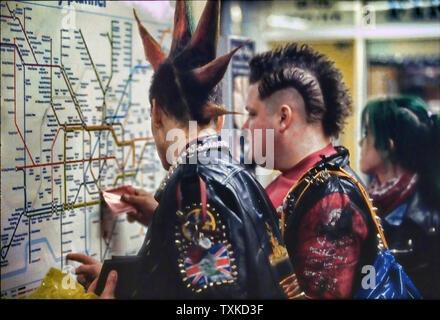 Punks checking tube map in London Underground, England, UK. - Stock Photo
