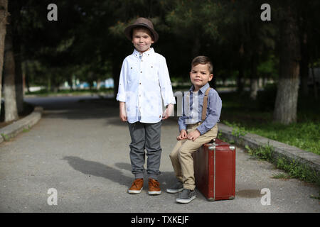 two Caucasian boy brothers in vintage clothes. One sits on an old suitcase, the other stands next to - Stock Photo