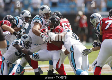 Carolina Panthers defensive end Tyler Brayton (96) and defensive end Julius Peppers (90) wrap up Atlanta Falcons running back Michael Turner (33) at the line of scrimmage in the first quarter at Bank of America Stadium on September 28, 2008 in Charlotte, North Carolina.   (UPI Photo/Bob Carey) - Stock Photo
