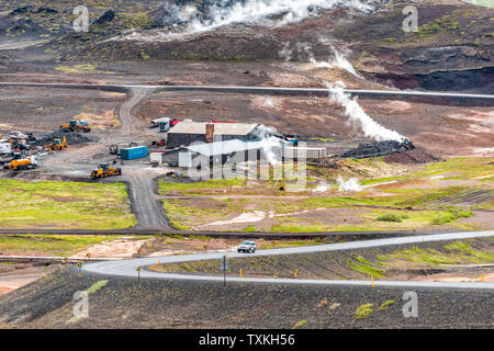 Reykjahlid, Iceland - June 16, 2018: Landscape high angle view near lake Myvatn and steam vents during cloudy day by house and ring road - Stock Photo