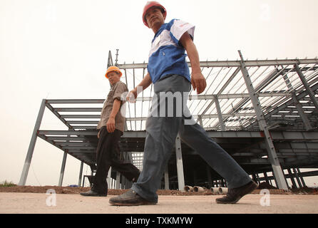 Chinese workers walk past a new auto assembly plant under construction near Chang'an Ford's first automobile assembly factory in Chongqing August 25, 2010. Chang'an Ford is Ford Motor Company's China car-making joint venture.  China is the hottest auto market by number of vehicles sold, and automakers are looking to the country to drive revenues amid weak global demand.   UPI/Stephen Shaver - Stock Photo
