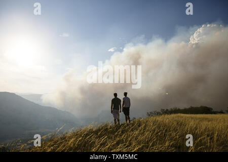 Colorado Springs resident Robert Demski (left) and his friend Ben Russi watch the winds push the Waldo Canyon Fire into the Garden of the Gods and Mountain Shadows neighborhoods in Colorado Springs, Colorado on June 26, 2012.  The fire exploded Tuesday afternoon after dramatic shifts in the wind and destroyed numerous homes.  UPI/Trevor Brown Jr.